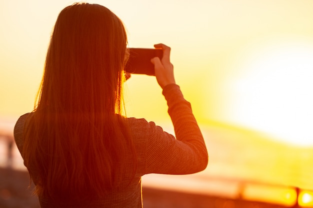Una giovane donna fotografa il tramonto sulla spiaggia.