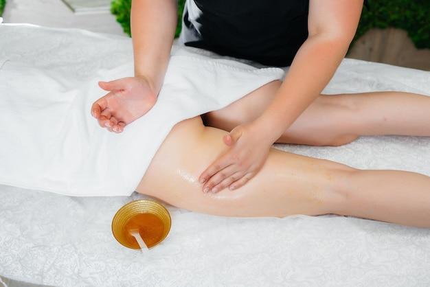 Una giovane donna graziosa sta godendo di un massaggio professionale con miele presso la spa.