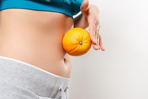 Una giovane donna in abiti sportivi tiene un'arancia sul suo stomaco