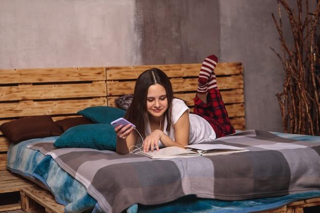 Una giovane donna in cuffia e con un telefono cellulare in mano ascolta le lezioni e guarda un libro sdraiata sul letto. formazione online, tempo libero.