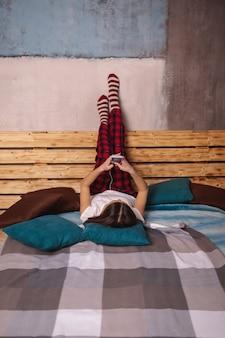 Una giovane donna in cuffia e con un telefono cellulare in mano giace sul letto con le gambe alzate. una ragazza si fotografa al telefono.