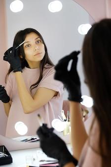 Una giovane donna in guanti pettina le sopracciglia in un salone di bellezza