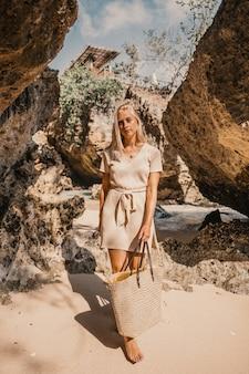 Una giovane donna in piedi accanto alle scogliere durante il giorno