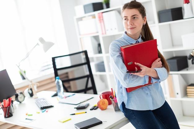 Una giovane donna in ufficio è in piedi, appoggiata a un tavolo e tiene in mano un telefono e una cartella con documenti.