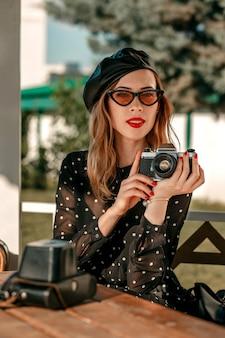 Una giovane donna in un abito vintage nero a pois con una vecchia macchina fotografica in mano in posa sulla strada