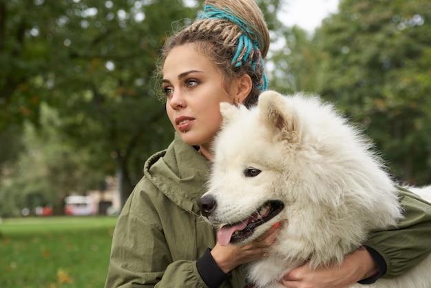 Una giovane donna in un cappotto verde e con i dreadlocks in testa a riposo con il suo cane samoiedo nel parco
