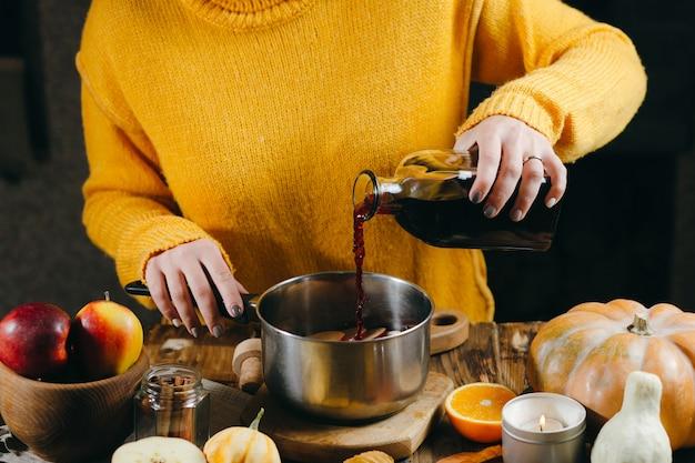Una giovane donna in un pullover caldo, lavorato a maglia e giallo sta versando il vino dalla bottiglia di vetro in una padella per fare vin brulè caldo