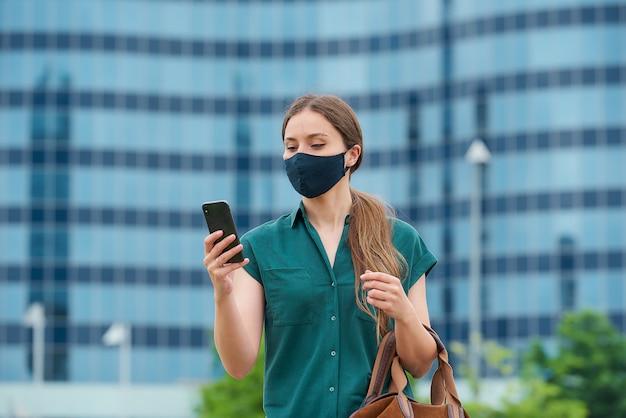 Una giovane donna in una maschera medica blu navy per evitare la diffusione del coronavirus che tiene la sua borsa di pelle
