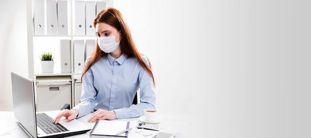 Una giovane donna in una maschera protettiva lavora su un computer. donna d'affari in una maschera medica in ufficio.