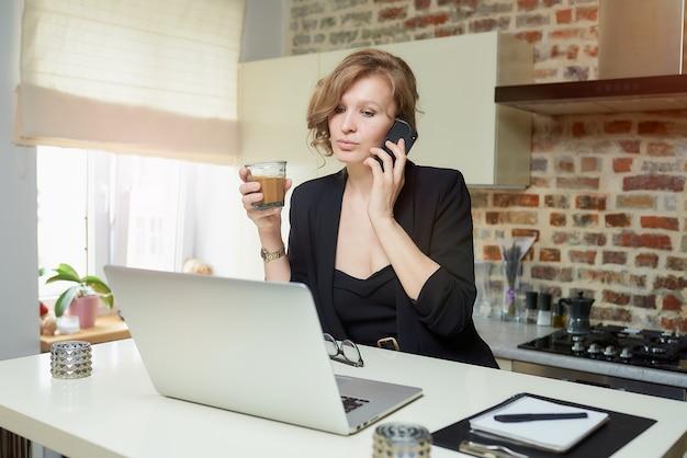 Una giovane donna lavora a distanza nella sua cucina. una ragazza felice facendo chiamate e tenendo un bicchiere di caffè a casa. una signora bionda si prepara per una lezione su una videochiamata.
