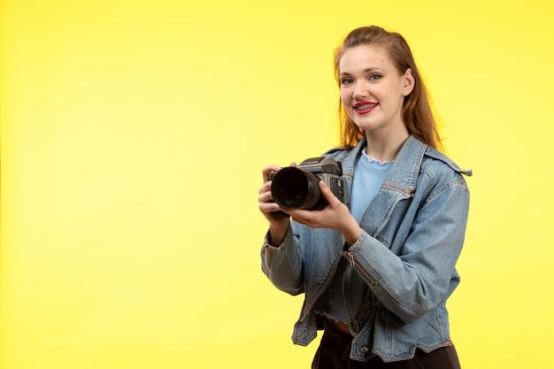 Una giovane donna moderna di vista frontale in pantaloni neri della camicia blu e cappotto di jeans che posano la macchina fotografica sorridente della foto della tenuta di espressione felice