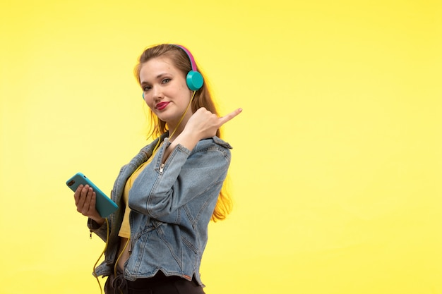 Una giovane donna moderna di vista frontale in pantaloni neri della camicia gialla e cappotto di jeans con le cuffie colorate facendo uso della posa del telefono