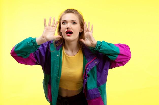 Una giovane donna moderna vista frontale in camicia gialla pantaloni neri e giacca colorata in posa sorpreso