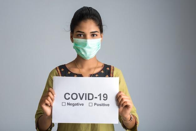 Una giovane donna o una ragazza in una maschera medica in possesso di una tavola dell'epidemia di coronavirus, covid-19