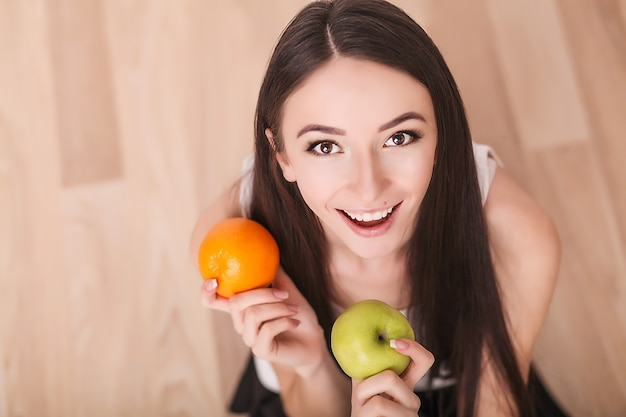 Una giovane donna osserva la sua figura e mangia frutta fresca.