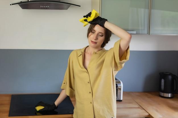 Una giovane donna pulisce in cucina, lava i piatti. è stanca e non soddisfatta del fatto che deve farlo.
