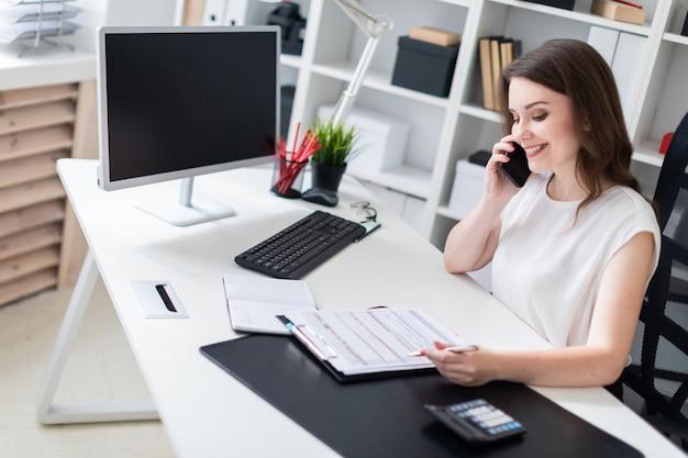 Una giovane donna seduta in ufficio alla scrivania del computer, parlando al telefono e prendere appunti sul foglio.