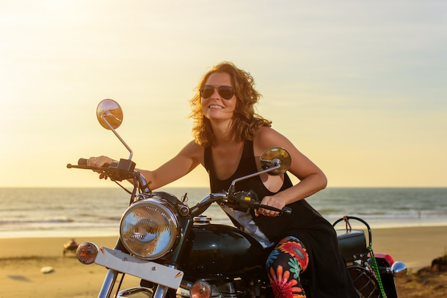 Una giovane donna sexy in occhiali da sole si siede sulla moto cromata nera