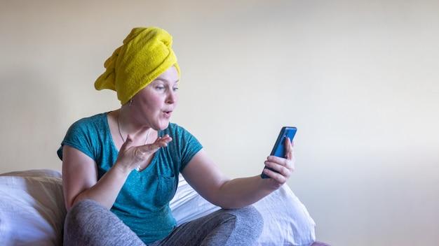 Una giovane donna si siede sul letto e guarda il gadget. il concetto di quarantena e autoisolamento.
