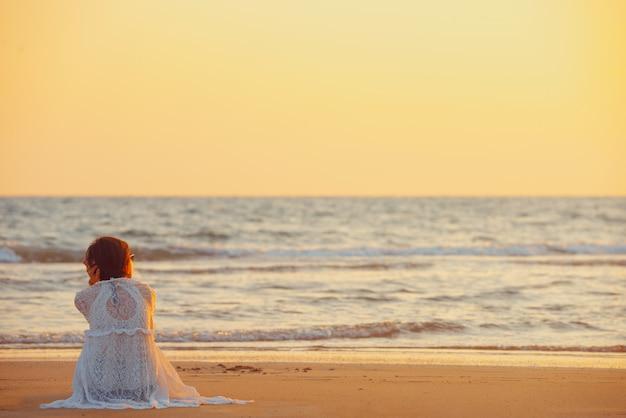 Una giovane donna si trova sulla spiaggia durante un tramonto, le vacanze estive.