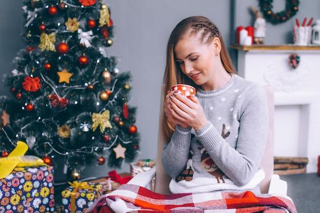 Una giovane donna siede avvolta in una coperta scozzese con una tazza di caffè caldo accanto al camino vicino all'albero di capodanno.
