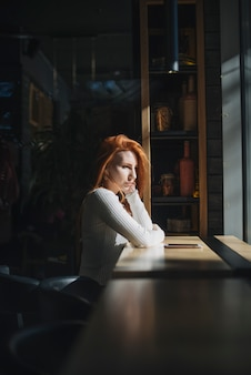 Una giovane donna solitaria che si siede vicino alla finestra con il telefono cellulare sul tavolo