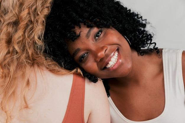 Una giovane donna sorridente africana che si appoggia sulla spalla della sua amica con la pelle bianca