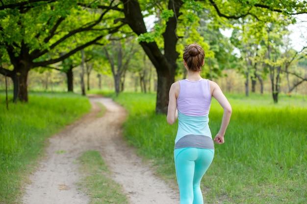 Una giovane donna sportiva in esecuzione in una foresta verde di fine estate. sport e benessere
