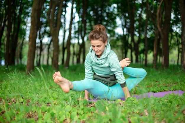 Una giovane donna sportiva pratica yoga in una foresta estiva verde chiusa, yoga assans postura. meditazione e unità con la natura