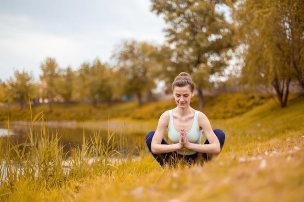 Una giovane donna sportiva pratica yoga su un prato giallo in autunno vicino al fiume, usa yoga assans postura. meditazione e unità con la natura
