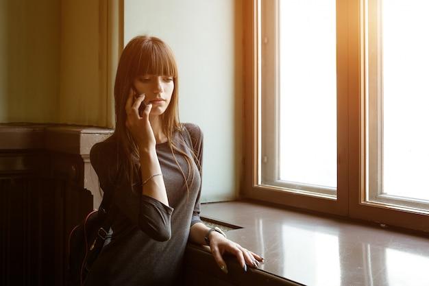 Una giovane donna sta alla finestra a parlare al telefono
