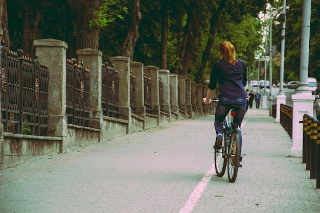 Una giovane donna sta pedalando verso il tramonto nell'annata del parco
