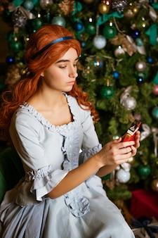 Una giovane donna su un albero di natale con un giocattolo in mano in un bellissimo abito blu vintage