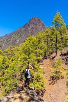 Una giovane donna sul bellissimo sentiero di trekking di la cumbrecita sull'isola di la palma vicino alla caldera de taburiente, isole canarie. spagna