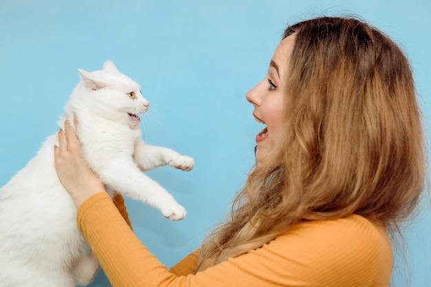 Una giovane donna tiene in braccio un gatto bianco.