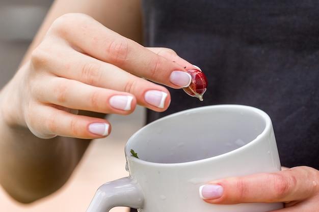 Una giovane donna tiene una tazza e una bacca di uva spina