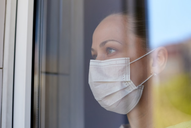 Una giovane donna triste in una maschera medica in quarantena guarda fuori dalla finestra.