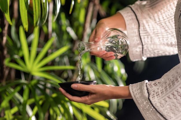Una giovane donna versa l'olio da massaggio in una ciotola. preparazione per trattamenti benessere. avvicinamento