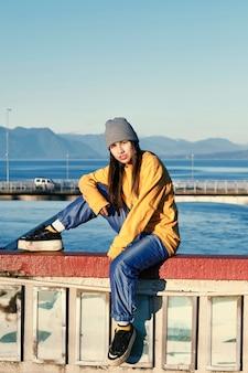 Una giovane donna vestita di hip-hop seduta su un ponte sospeso su un lago