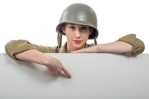 Una giovane donna vestita in uniforme militare americana ww2 che mostra insegna vuota vuota