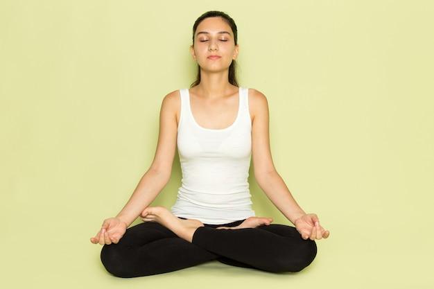 Una giovane donna vista frontale in camicia bianca e pantaloni neri in posa seduta in meditazione yoga posa sullo sfondo verde ragazza posa modello bellezza giovane emozione sport yoga