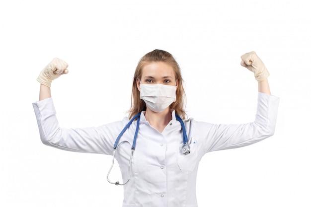 Una giovane dottoressa in vista frontale bianco vestito medico con stetoscopio indossando maschera protettiva bianca in guanti flettendo sul bianco