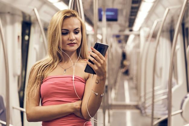 Una giovane e bella donna della metropolitana usando il suo telefono cellulare