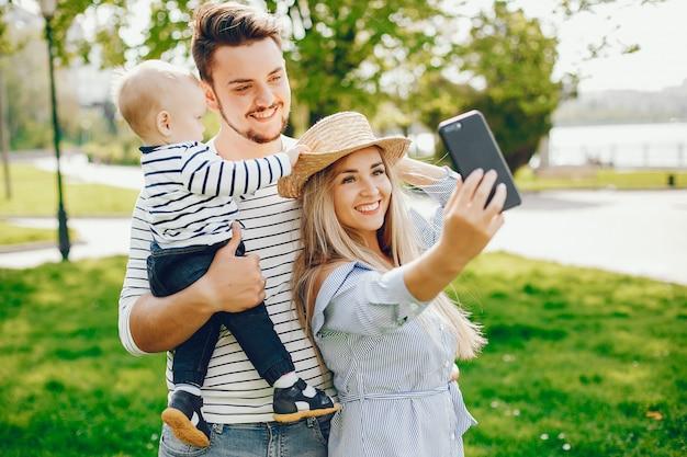 Una giovane e bella madre bionda in un vestito blu, insieme al suo bell'uomo