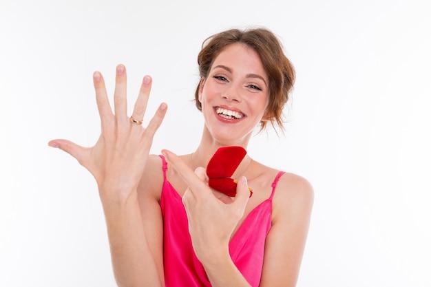 Una giovane e bella ragazza con capelli castani ondulati, pelle pulita, denti piatti, un bel sorriso, in una maglia rosa, tiene in mano un anello da allenamento, mostra l'anello di fidanzamento sulla sua mano e si rallegra