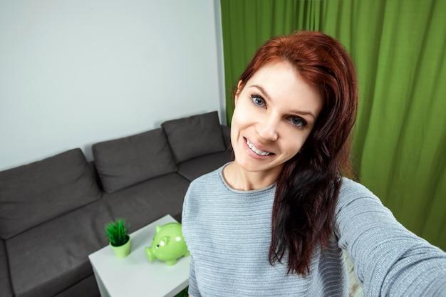 Una giovane e bella ragazza è seduta di fronte a una dslr e sta registrando un vlog