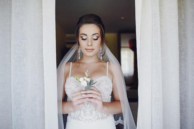 Una giovane e bella sposa a casa in piedi vicino alla finestra con i fiori
