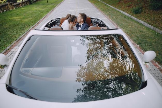 Una giovane e bella sposa è seduta in una macchina con suo marito