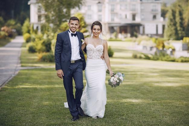 Una giovane e bella sposa e suo marito in piedi in un parco estivo con bouquet
