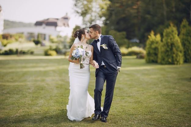 Una giovane e bella sposa e suo marito in piedi nel parco con bouquet di fiori